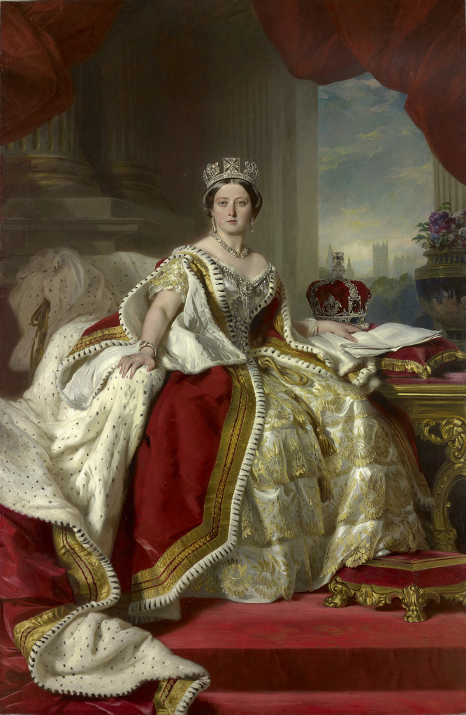 A full length portrait of Queen Victoria seated at a desk. She wears a white and gold gown with a tiered skirt, an ermine-lined robe and a tiara. On the table beside her is the Imperial State Crown, and her hand rests on a document. The carpet, curtains, and upholstered footstool are the same red as the queen's robe; in the background are the bases of some columns, a floral arrangement, and a view out the window to the distant Houses of Parliament.