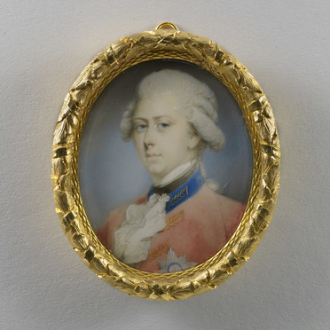 A miniature portrait of the young George IV in a gold frame. He has a solemn expression, powdered hair, and wears a red military uniform with blue collar, white cravat, and the Star of the Order of the Garter pinned to his breast. The frame has a decorative leaf pattern.