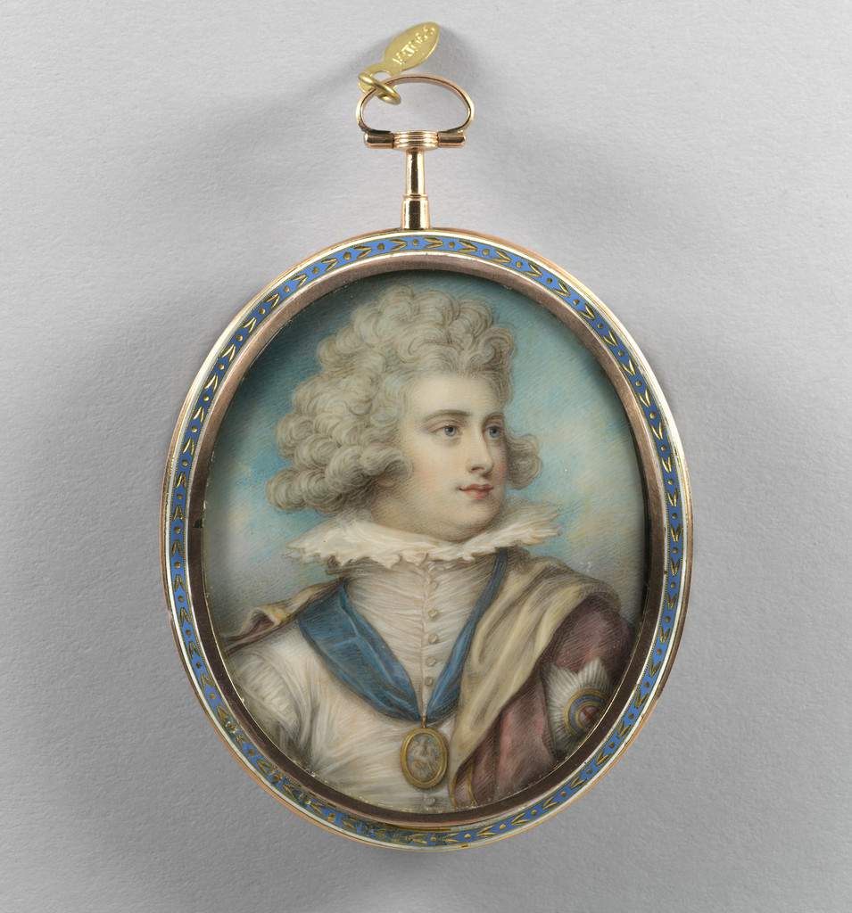 A miniature portrait in a blue and gold oval frame, with a ring attached so that it can be attached to a chain or worn as a pendant. The subject is George IV as a young man in seventeenth-century costume: he is in three-quarter profile, facing to the right. He has curly powdered hair and wears a cream doublet with a high starched collar; a miniature portrait, possibly of two women, is on a blue ribbon around his neck, and a pink cloak is draped across his shoulders, with the star of the Order of the Garter embroidered on the shoulder.
