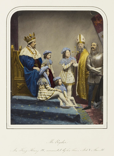 A photograph, hand-coloured in watercolour, of a group of actors performing in Richard II. On the left, in profile, John Ryder as Bolingbroke is seated on a gold-painted throne on a carpeted pedestal. He wears a royal blue cloak with an ermine collar over a red tunic, a gold chain of office, and an elaborate gold crown. He is surrounded by four boys: two sit at his feet, the other two stand beside and in front of him. All four children wear matching outfits: a cream tunic with gold embroidery, a pale blue collar with a zig-zag hem, a blue hat, white stockings, and one blue and one white shoe. In the background stands a bishop in mitre and gold robe, holding a crosier. On the right stands a soldier in plate armour and a chainmail hood.