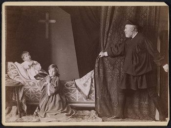 A photograph of an adult man and two children posing in a scene from Richard III. A small boy sits on a chaise-longue in a white night-shirt, his hands clasped in prayer and his gaze directed heavenward. On the floor in the foreground, a girl, slightly older, kneels on a fur rug; she wears a cloak with voluminous sleeves, and is also praying, but her gaze is directed outwards toward the viewer. On the right, a white bearded man in black tunic, boots, and hat is pulling back a brocade curtain. There is a cross on the back wall.