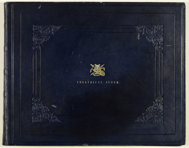 A large album, landscape format, bound in dark blue leather. Patterns are inlaid into the leather on the front cover, framing the gold embossed lettering saying 'Theatrical Album' and an emblem made up from a harp, theatrical mask, sword, arrow, and chain.