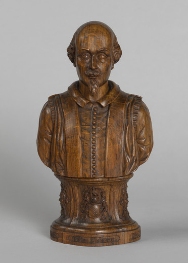 """A polished wooden bust of Shakespeare on a small plinth. """"William Shakespeare"""", """"Born 1564"""" and """"Died 1616"""" are carved around the base in a blackletter style. Shakespeare's coat of arms and the masks of comedy and tragedy are carved on the plinth. Shakespeare is recognisable by his bald head, short beard, and costume with a narrow collar and row of small buttons, based on that of his funerary monument in Statford."""
