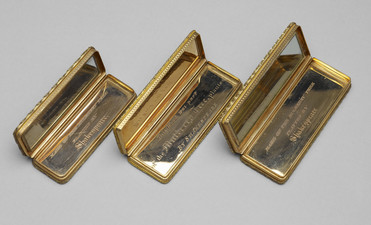 """Three gold-trimmed rectangular boxes, each open at the hinge to display a mirrored lining. Two of them have inscriptions reading 'Made of the Mulberry Tree planted by Shakespeare'. The central box has the inscription """"This Wood was part of the Mulberry Tree planted by Shakespeare."""""""
