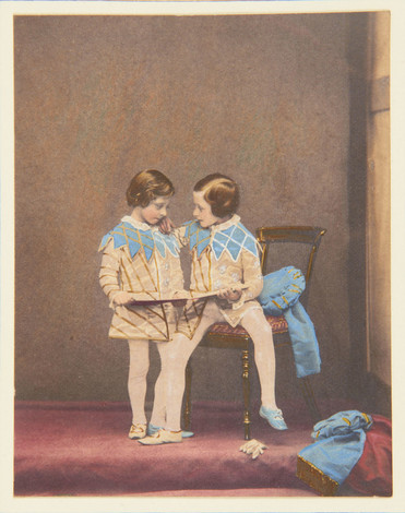 A photograph, hand-coloured in watercolour, of two children in medieval fancy dress: both wear short cream tunics with gold embroidery and pale blue collars with zig-zag hems, white stockings, and one blue and one white shoe. The taller child is perched on the edge of a Victorian wooden chair with an upholstered seat. He has his hand on the smaller child's shoulder, looking at him, as they both hold an opened folder or slim volume. Two blue fabric hats, matching the collars, have been discarded on the chair and the floor; a white glove is on the floor by the chair.